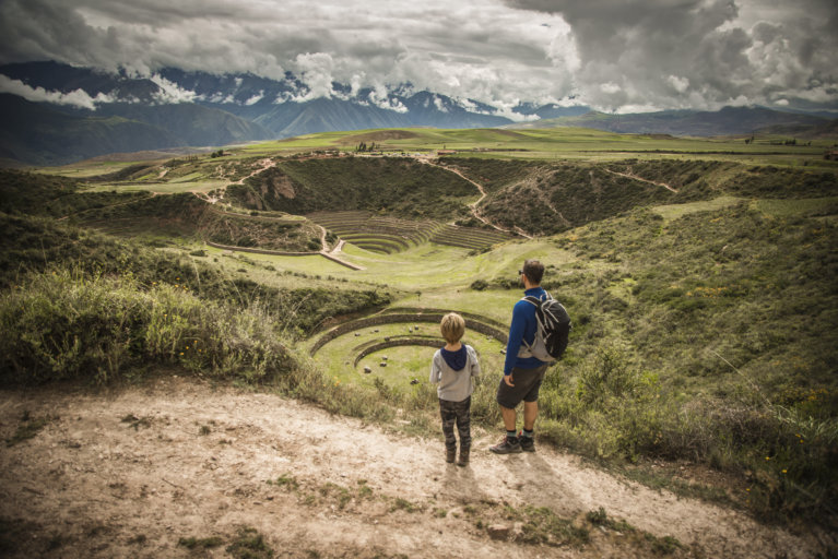 Father and son looking out towards the Moray ruins on a luxury tour of Peru