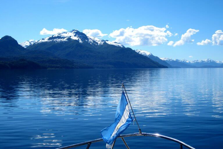 Lake and mountain views and Argentine flag visible during a private boat tour of the Argentine Lake District