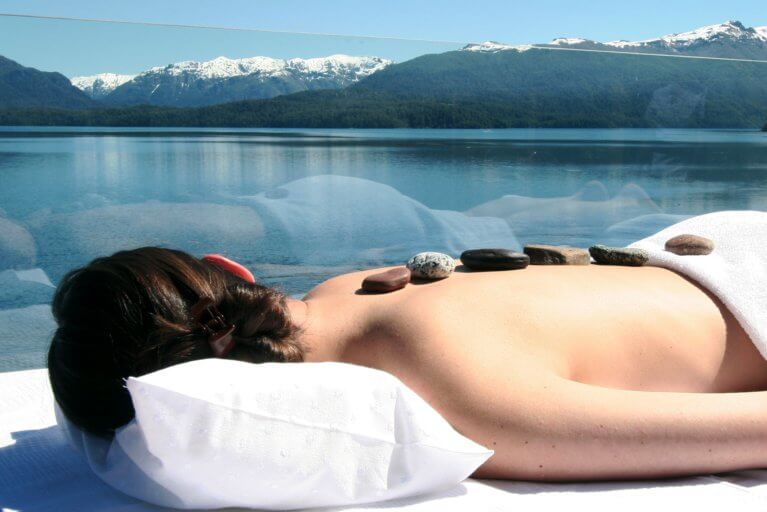 Woman enjoying a luxury spa treatment outdoors with views of the Lake District on a luxury Argentina trip