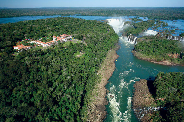 Bird's eye view of luxury Hotel das Cataratas, greenery, river and Iguassu Falls