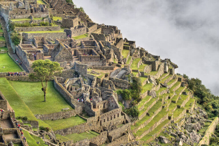 View of the side of Machu Picchu against misty cloud on a luxury Peru tour