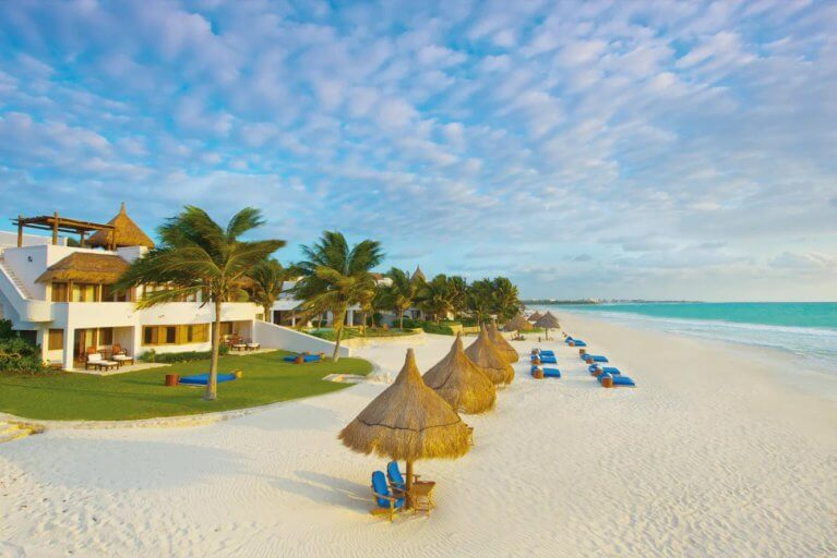 White sand, privte sun loungers and palm trees on Maroma Beach on a luxury trip to the Yucatan