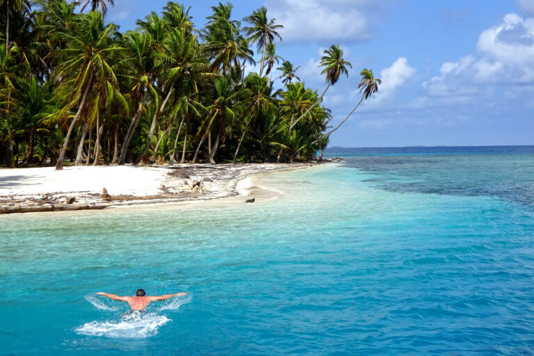 Man swimming in turquoise waters in the San Blas archipelago near a tropical palm-fringed beach during a private Panama tour
