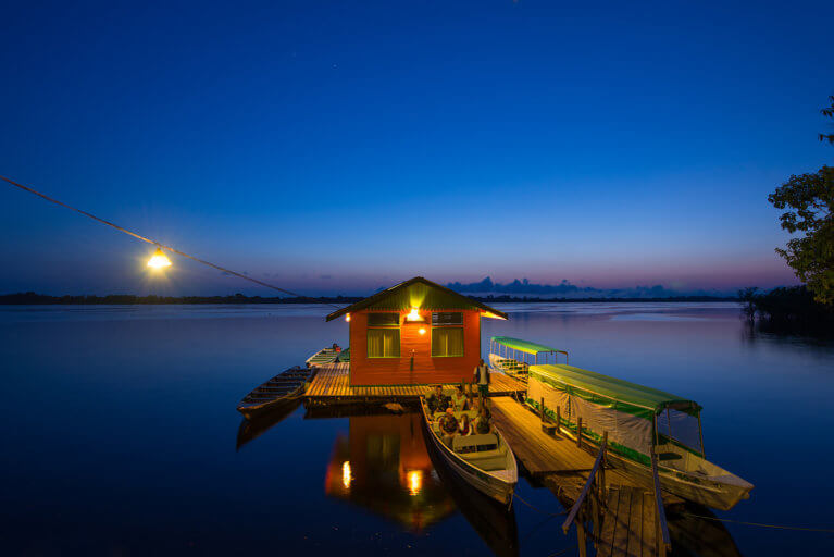 A family takes a private boat tour of the Amazon by night at Anavilhanas Jungle Lodge