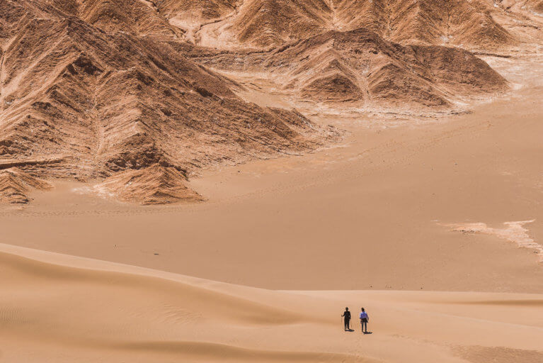 Two people hiking in the distance on a private Atacama tour