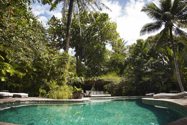 Outdoor pool at Casa Uxua with trees in the background during luxury brazil trip