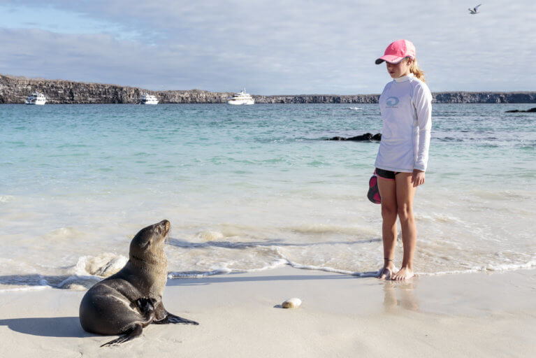 Girl and seal facing each other on a beach on a luxury tour of the Galapagos Islands