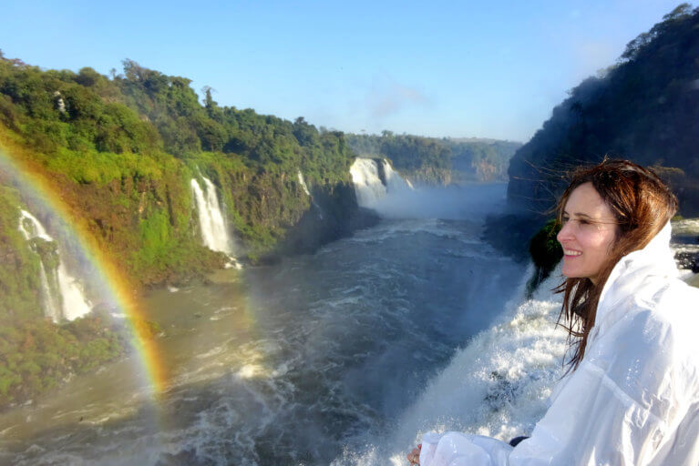 Woman on a private tour looking out towards Iguassu Falls with a rainbow over the river