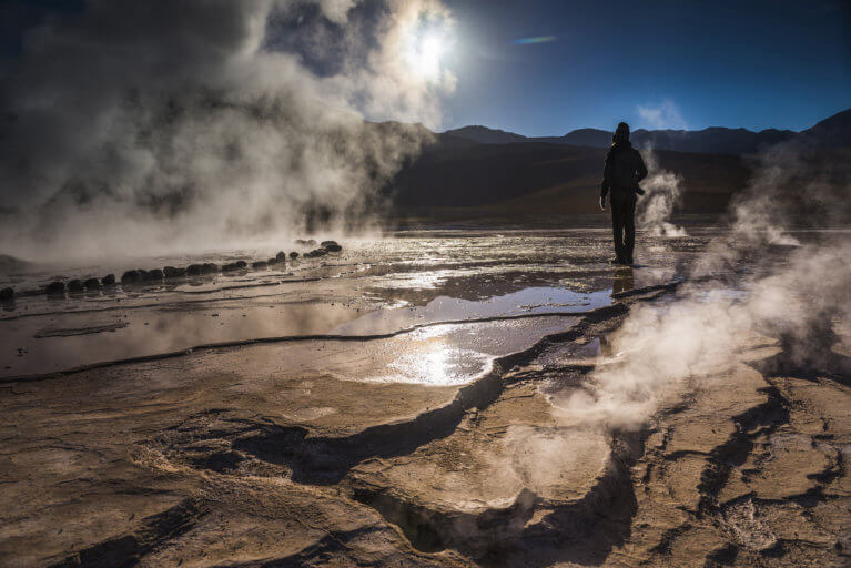 Man standing next to Geyser El Tatio with mist on a luxury Chile tour