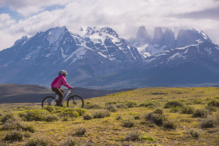 One woman biking on a private Patagonia tour, with views of snowy mountain