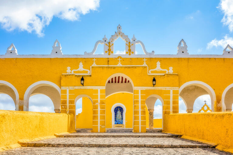 Private tour of the Yucatan and the yellow convent of San Antonio de Padua against a blue sky in Izamal