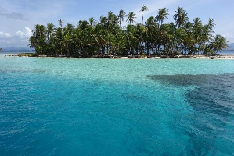 Clear turquoise waters and coconut-fringed beach of one the San Blas Islands during a luxury Panama tour