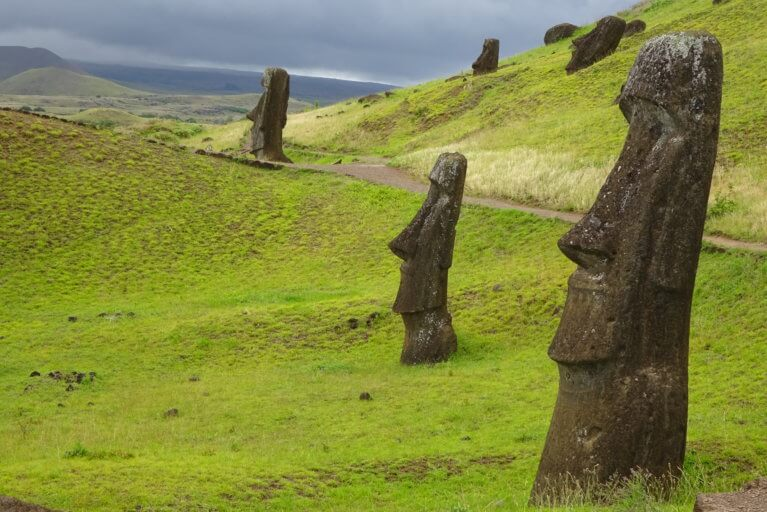 Sideways view of Moai statues and moody skies on a luxury trip to Easter Island