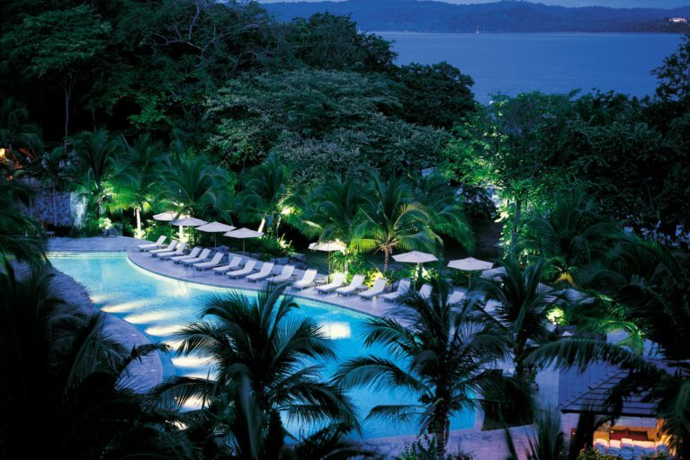 Four Seasons pool by night all lit up surrounded by palm trees on luxury trip to Costa Rica