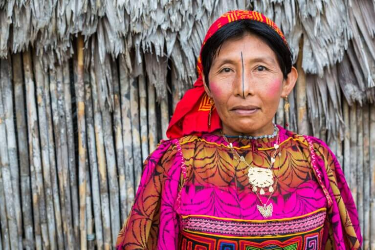 Close up portrait of a Guna lady in traditional colourful robes in front of a hut in the San Blas Islands during a private Panama tour
