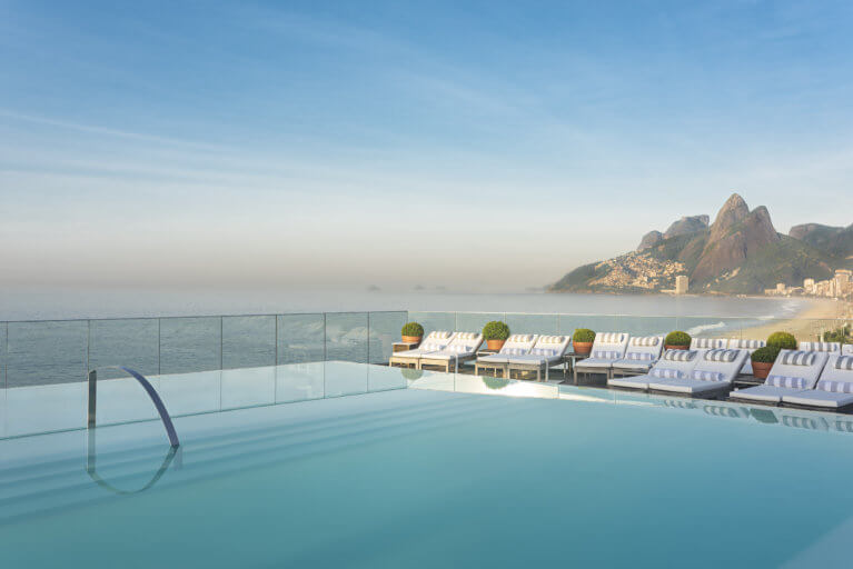 The pool and sunloungers at Hotel Fasano in Rio, with the beach and mountains in the background on a luxury trip to Brazil