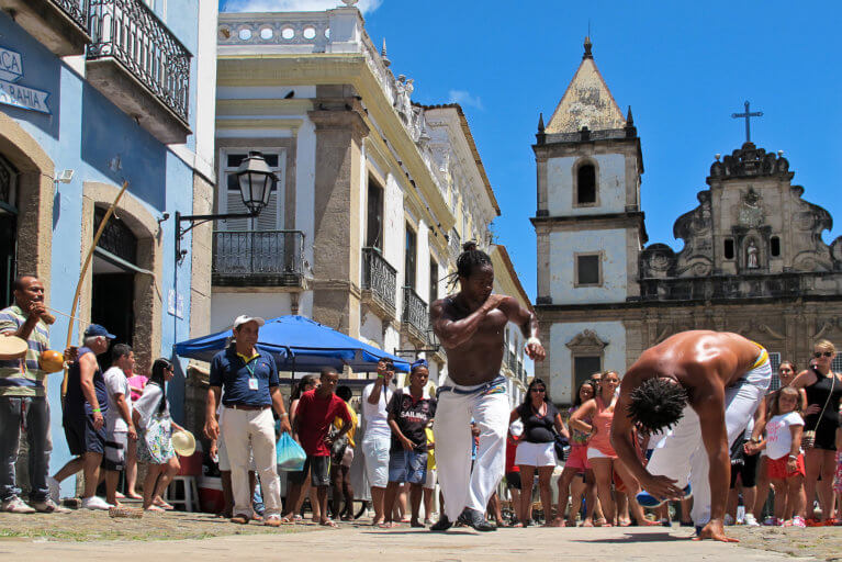 Two men performing capoeira to a crowd on the streets of Pelourinho in Salvador as seen on a luxury Blue Parallel trip to Brazil