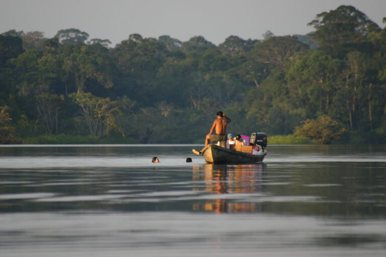 Residents of the Amazon on small boat and swimming in river
