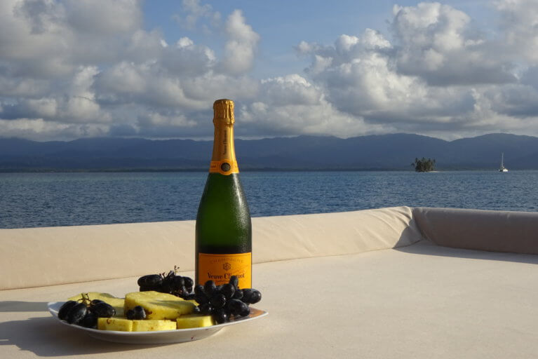 Champagne and fruit on the deck of a private yacht with sea views in Panama's San Blas Islands