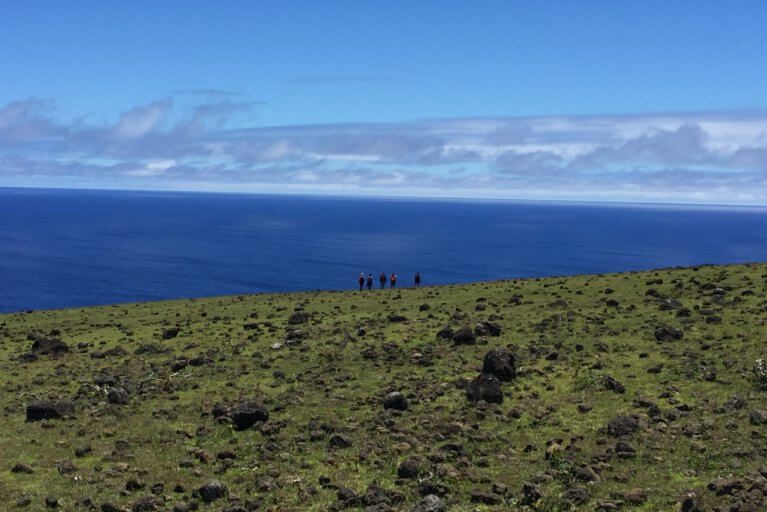 View of a small group in the distance looking out towards the sea on a private hiking tour in Easter Island