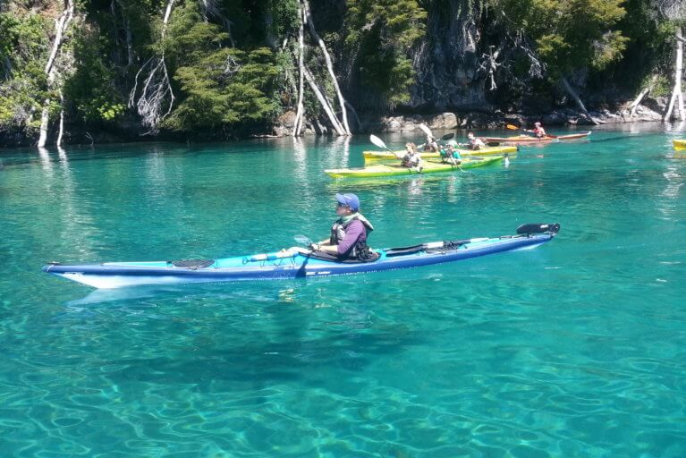 Woman enjoying a private kayaking tour on crystal clear waters in Argentina's Lake District