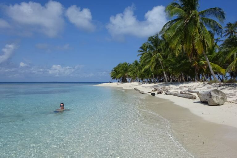 Swimming in clear waters by a tropical beach in the San Blas Islands on a private tour of Panama