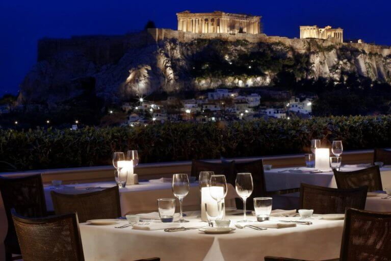 Romantic dinner with views of Acropolis lit up at night during luxury Greece tour