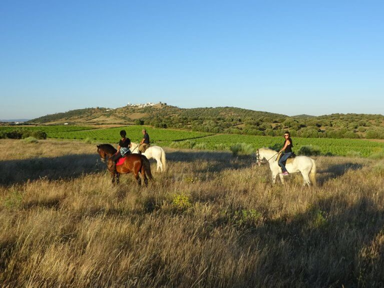 Three people horseback riding in Alentejan countryside with Monsaraz in background during a luxury Portugal tour