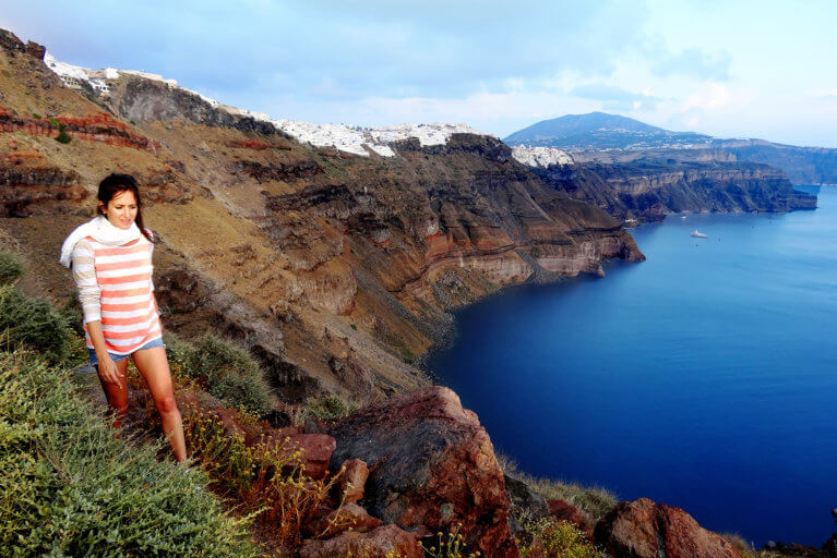 Woman hiking on Skaros Rock in Santorini with sea views