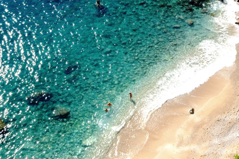 Aerial view of two people walking on deserted beach during luxury Croatia trip