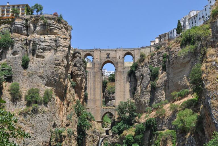 View of Ronda bridge from below against a blue sky during a luxury Spain trip