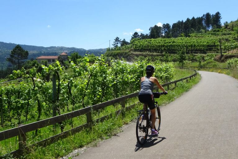 A girl biking in the Douro Valley on a sunny day during a luxury Portugal trip