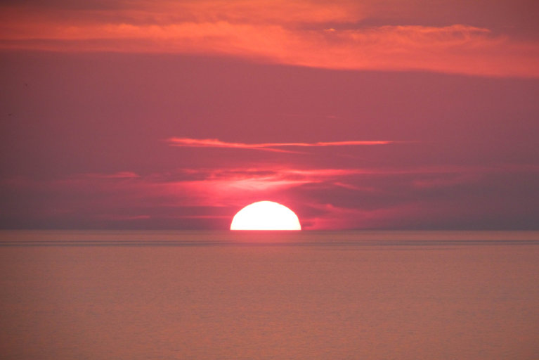Pink sunset over the water in the Aeolian Islands during luxury Sicily tour