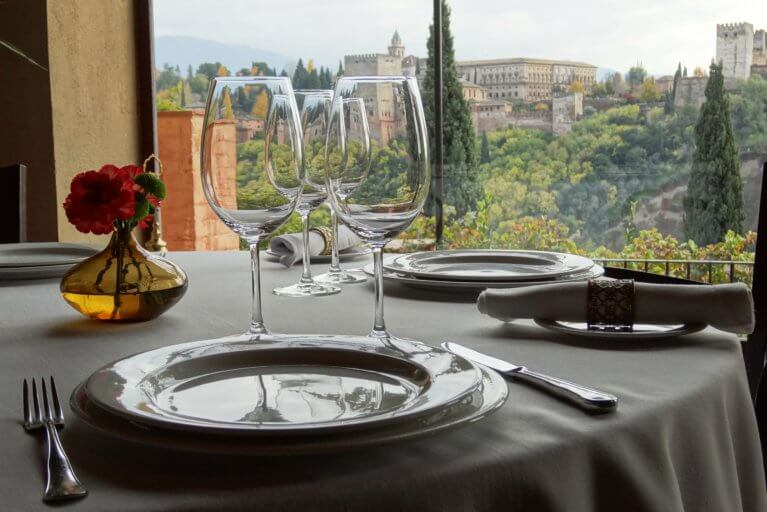 Plates set for a gourmet meal at Restaurante Juan Ranas with Alhambra views on a luxury trip to Spain