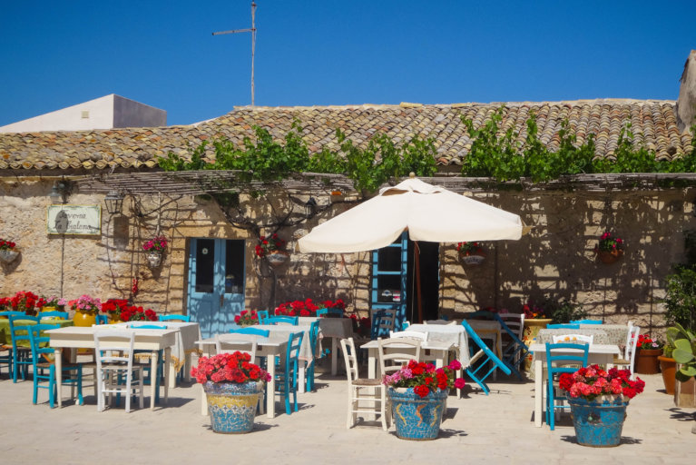 Outdoor tables at restaurant in fishing town Marzamemi during luxury Sicily trip