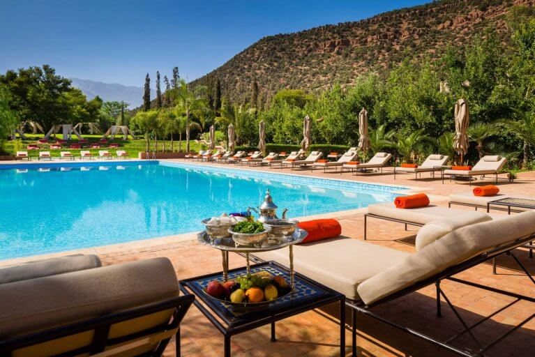Outdoor pool at Kasbah Tamadot with Atlas Mountain backdrop during luxury Morocco tour