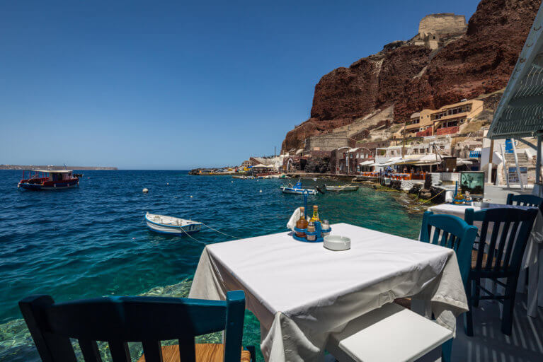 Table in a taverna with sea views beside the Red Cliffs in Amoudi Bay