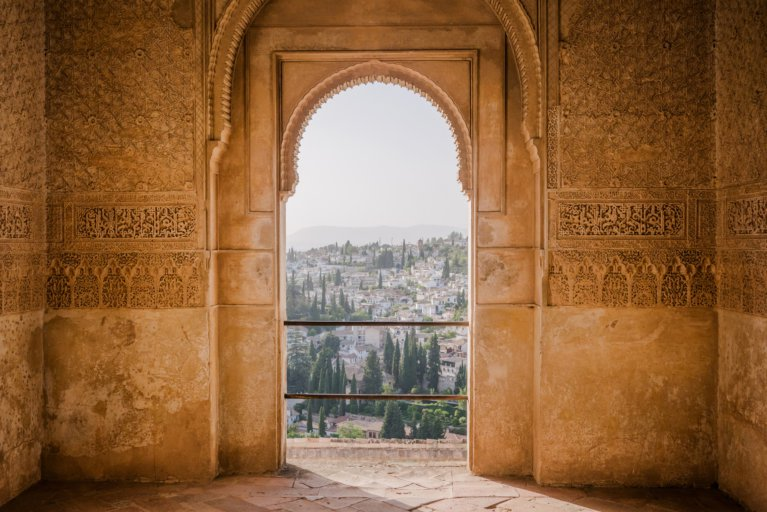 Intricate detail of architecture on arched window at the Alhambra Palace and views of Granada beyond on a private tour of Andalusia